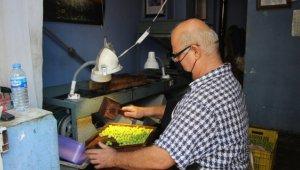 Bahçesinden topladığı zeytinleri ahşap tokmakla kırarak müşterileriyle buluşturuyor