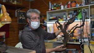 Emekli memur, deniz kıyısından topladığı ağaç parçalarına hayat veriyor